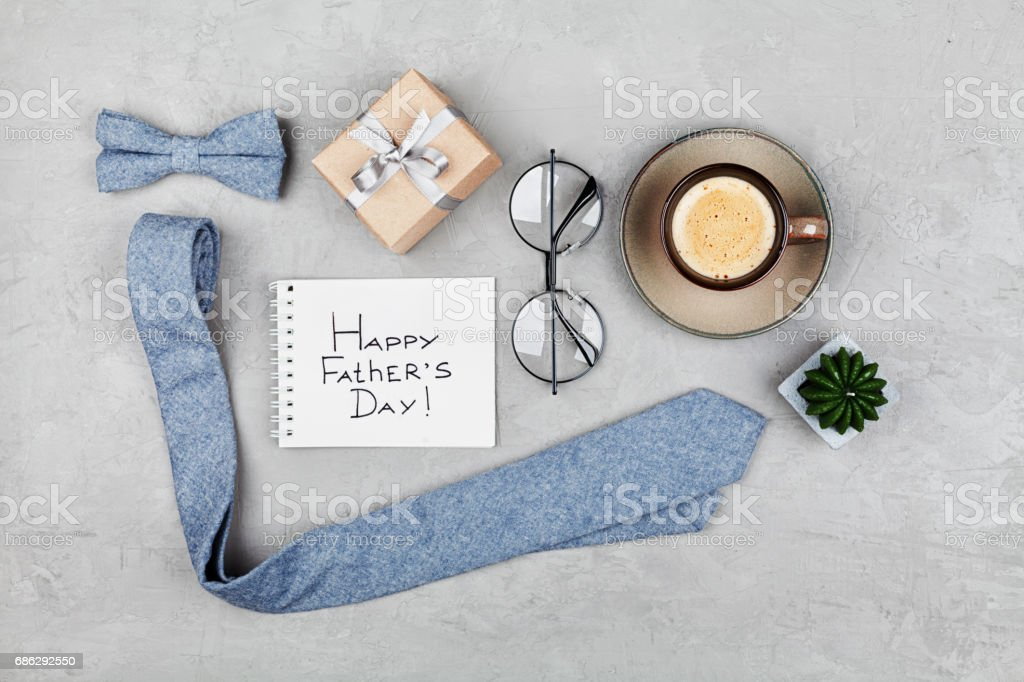 Happy Fathers Day background with morning coffee mug, gift, glasses, necktie and bowtie. Flat lay. stock photo