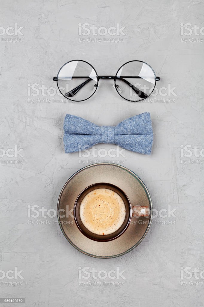 Happy Fathers Day background with morning coffee mug, glasses and bowtie on stone gray table. Flat lay. stock photo