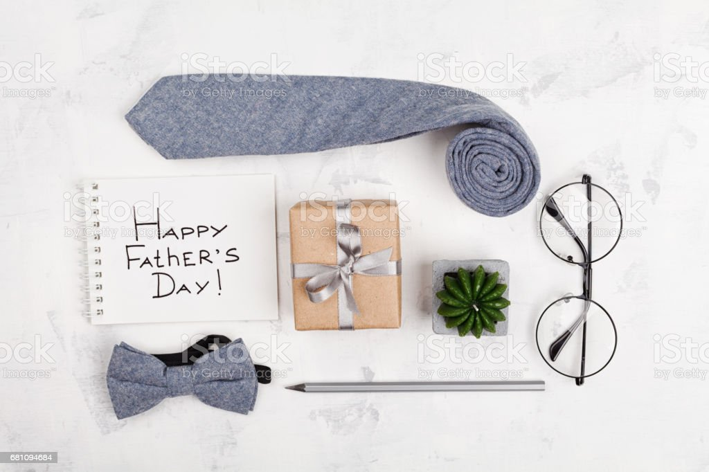 Happy Fathers Day background with notebook, gift, glasses, necktie and bowtie. Flat lay. stock photo