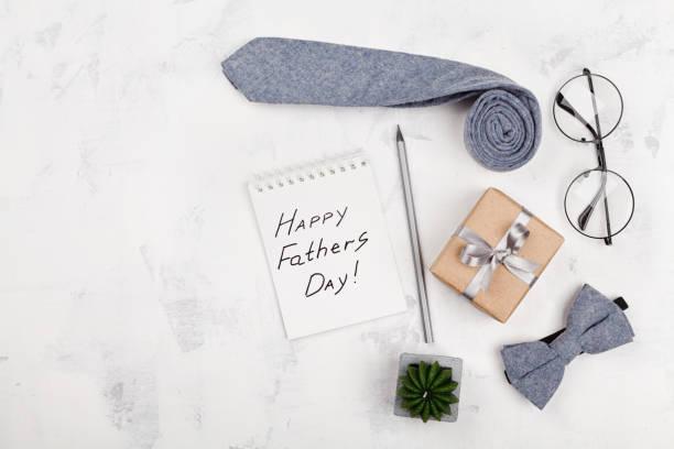 happy fathers day hintergrund mit notebook, geschenk, brille, krawatte und fliege. flach zu legen. - vatertagsgrüße stock-fotos und bilder