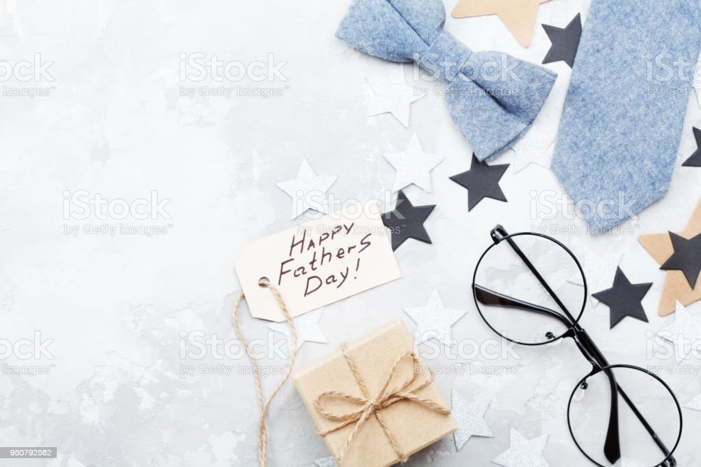 Happy Fathers Day background with paper tag, gift, glasses, necktie and bowtie on stone table top view. stock photo