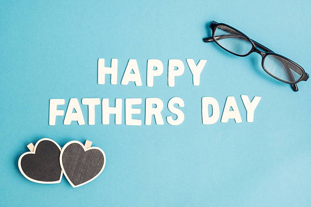 Happy Father's Day, black glasses, hearts on blue background stock photo