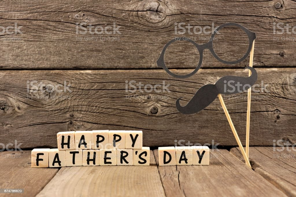 Happy Fathers Day blocks with mustache and glasses against wood stock photo