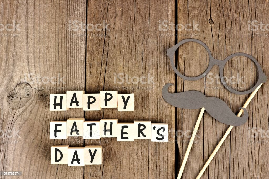 Happy Fathers Day blocks with mustache and glasses on wood stock photo