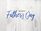 Happy Father's Day Blue Calligraphy Script Over White Wood Texture Background