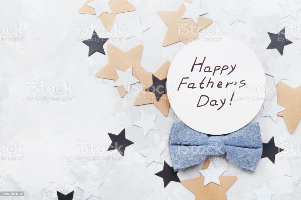 Happy Fathers Day card decorated bowtie and stars on stone table top view in flat lay style. stock photo