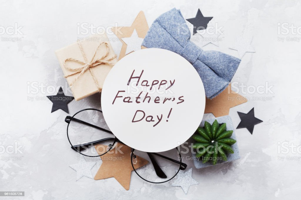 Happy Fathers Day card decorated bowtie, eyeglasses, gift box and stars on stone table top view. Flat lay. – zdjęcie