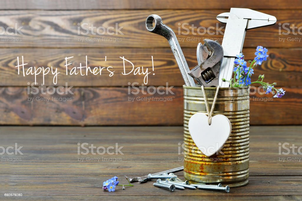 Happy Fathers Day card with tools, heart and flowers on wooden background stock photo