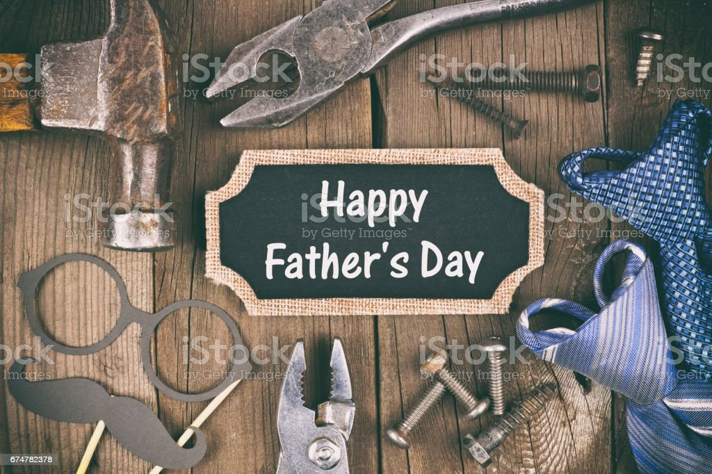 Happy Fathers Day chalkboard tag with tool, gift and tie frame on wood stock photo