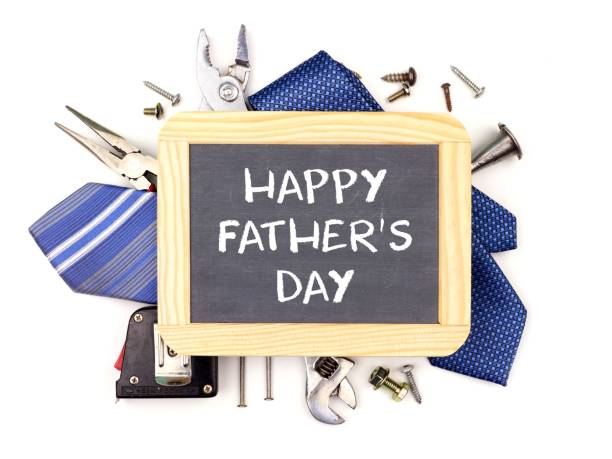 Happy Fathers Day chalkboard with underlying frame of tools and ties isolated on white stock photo