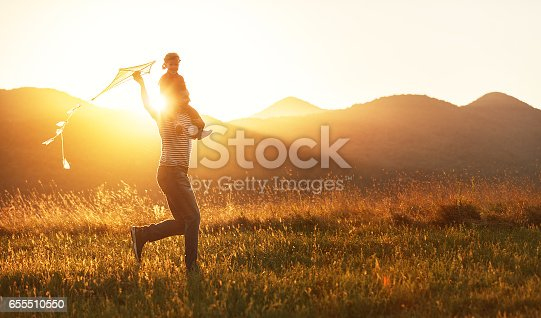 istock Happy father's day! Child girl and dad with a kite on nature in summer 655510550