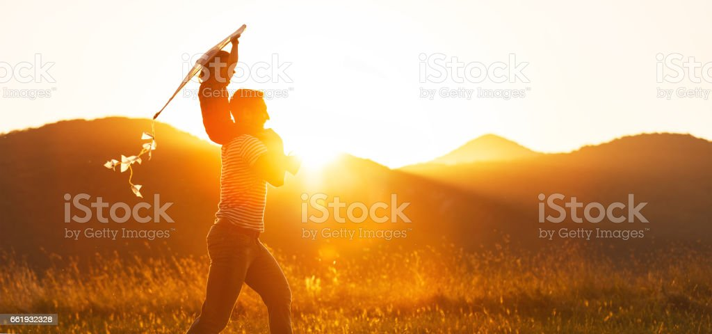 Happy father's day! Child girl and dad with a kite on nature in summer royalty-free stock photo
