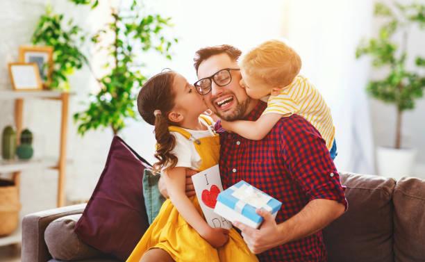 Glücklicher Vatertag! Kinder gratulieren Papa und gibt ihm Geschenk und Postkarte – Foto