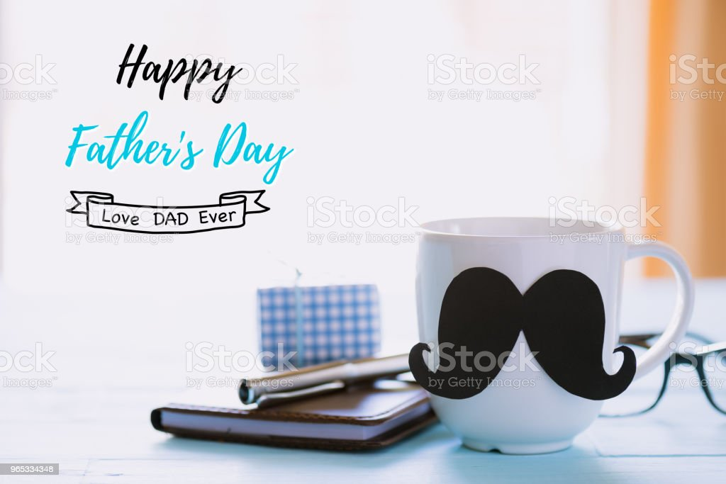 Happy fathers day concept. beautiful gift box, glasses, notebook, pen and coffee cup with black mustache on wooden table background. royalty-free stock photo