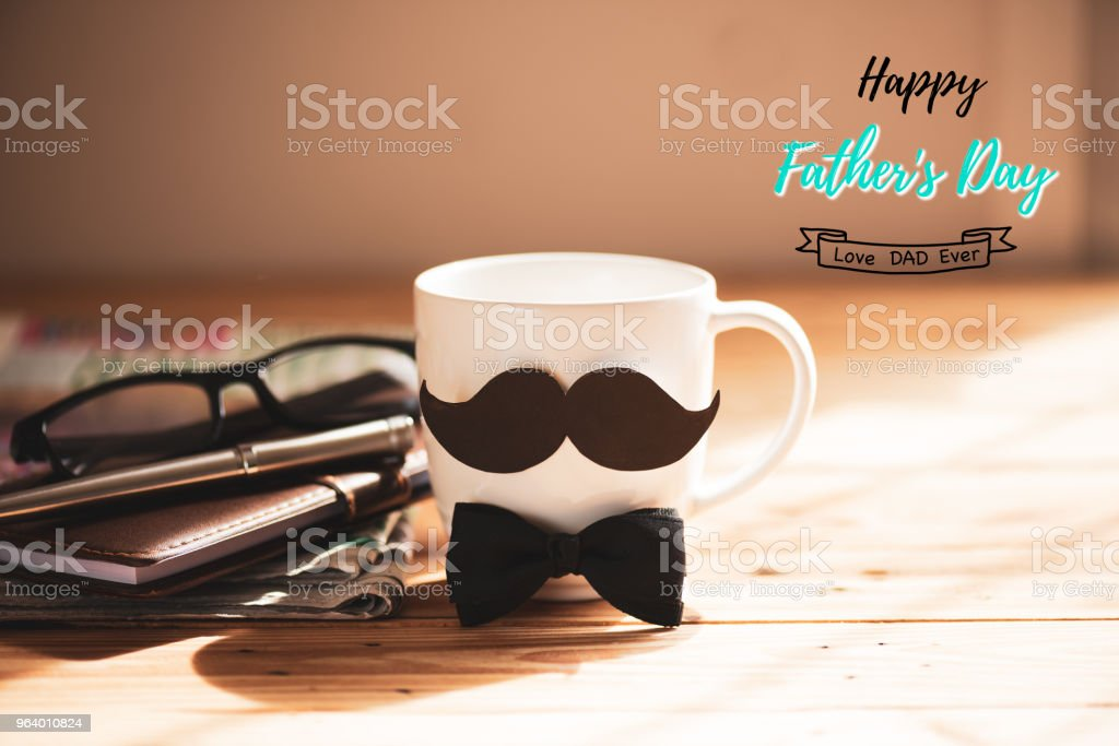 Happy fathers day concept. coffee cup with black paper mustache and newspaper, note book, glasses on wooden table background. - Royalty-free Adult Stock Photo