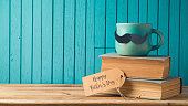 Happy Fathers day concept with coffee cup, mustache and books over wooden background
