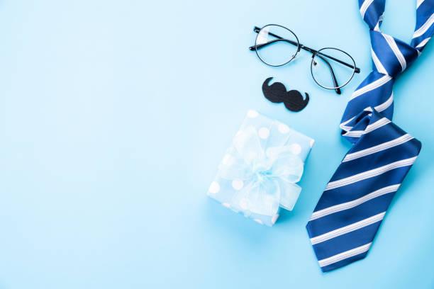 Glückliche Väter Tageskonzept. Oberansicht der blauen Krawatte, schöner Geschenkbox, Gläser und Schnurrbart auf strahlend blauem Pastellhintergrund. Wohnung gelegt. – Foto