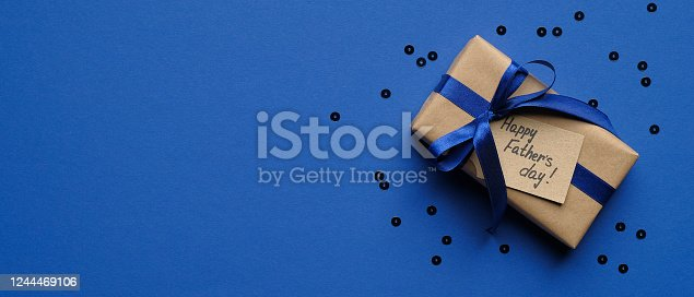 Happy Fathers Day concept. Wide banner mockup with gift box wrapped craft paper with blue ribbon and label Happy Father's Day on blue background with confetti. Fathers Day sale promotion poster design