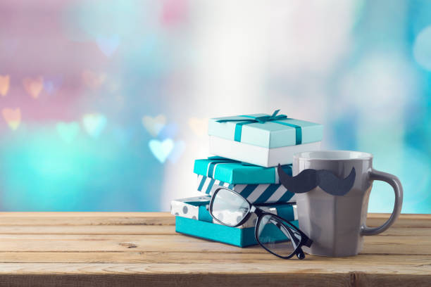 Happy Fathers day concept with coffee cup, mustache and gift box on wooden table over beautiful bokeh background stock photo