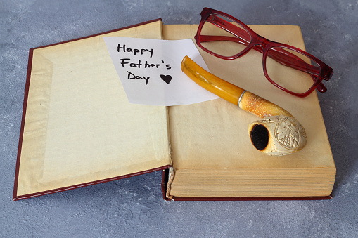 Happy Fathers day concept with pipe, glasses and books over wooden background