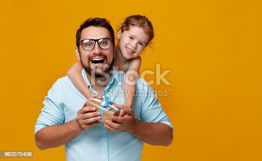 istock happy father's day! cute dad and daughter hugging on yellow background 962070408