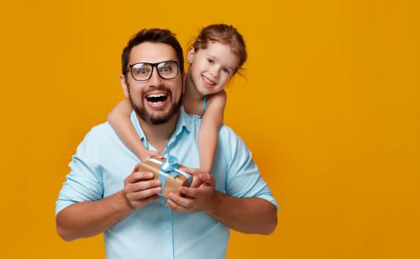 glückliche Vatertag! niedliche Papa und Tochter umarmt auf gelbem Hintergrund – Foto