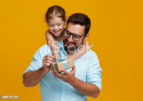 istock happy father's day! cute dad and daughter hugging on yellow background 966197782