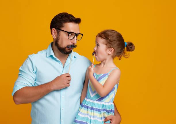 glückliche vatertag! lustige papa und tochter mit schnurrbart herumalbern auf gelbem hintergrund - schnurrbart themenpartys stock-fotos und bilder
