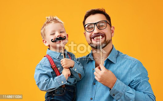 happy father's day! funny dad and son with mustache fooling around on colored yellow background