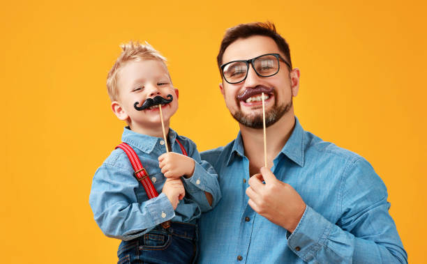 happy father's day! funny dad and son with mustache fooling around on yellow background - daddy stock pictures, royalty-free photos & images