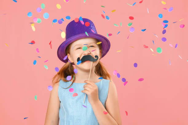 Happy father's day. Funny little girl with fake mustache and wearing a hat under falling confetti on a pink background. Family concept Happy father's day. Funny little girl with fake mustache and wearing a hat under falling confetti on a pink background. Family concept carnival children stock pictures, royalty-free photos & images