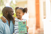 Happy Father's Day.  Little girl gives homemade card to her dad in front yard of family home.  African descent family.