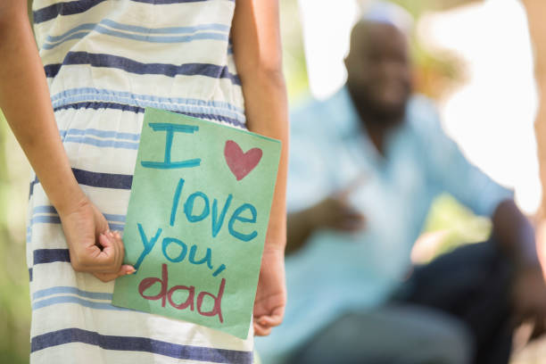 happy father's day. girl gives card to dad. - fathers day stock photos and pictures
