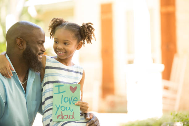 Happy Father's Day. Girl gives card to dad. stock photo