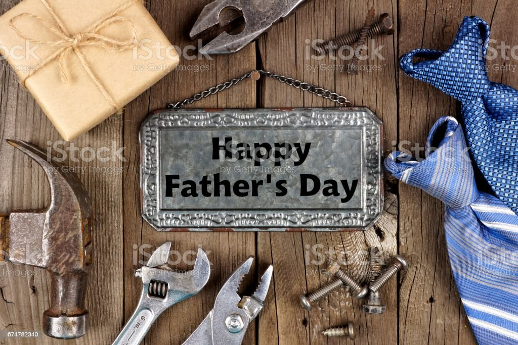 Happy Fathers Day metal sign with tool, gift and tie frame on wood stock photo