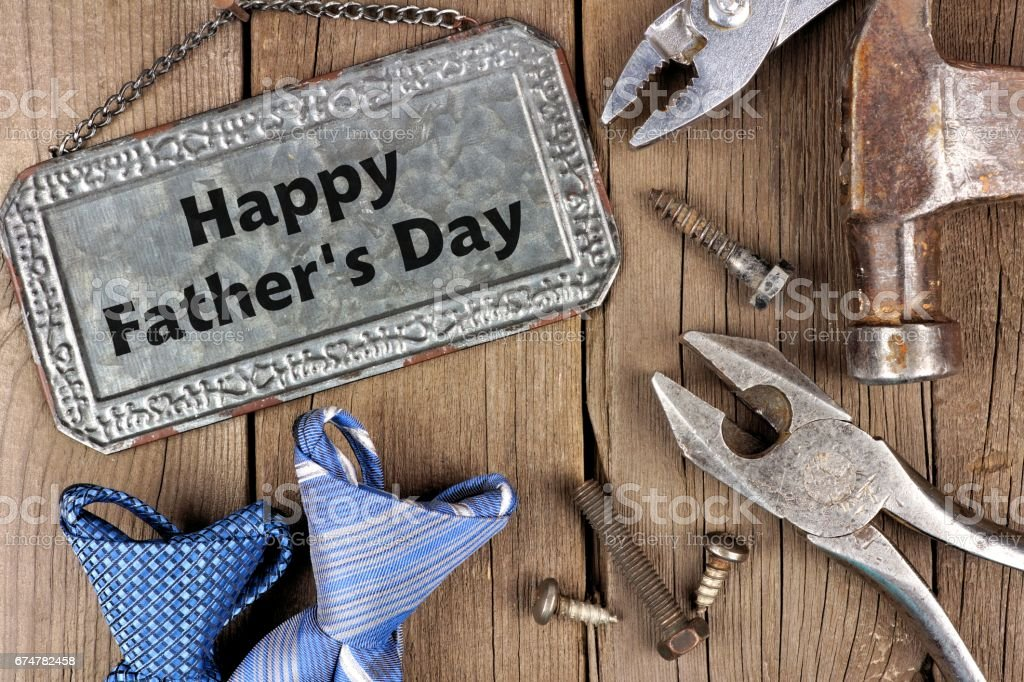Happy Fathers Day metal sign with tools and ties on wood stock photo