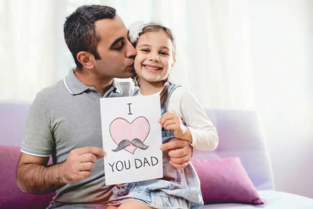 Glückliche Vatertag Portrait. Überrascht Papa hält Postkarte Geschenk und ihr lächelndes Kind küssen. – Foto