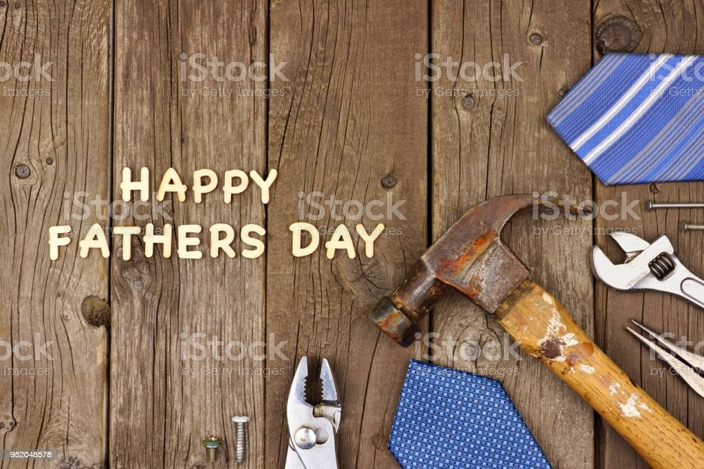 Happy Fathers Day wood letters with tools and ties on rustic wood stock photo