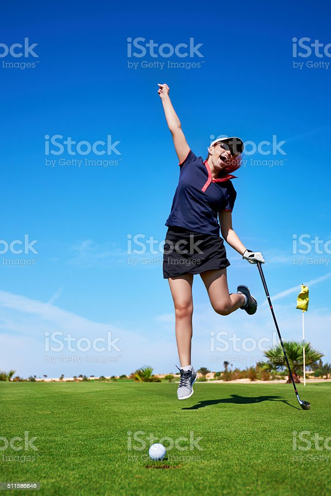 happy and winner golfer woman jumping on golf field and feeling...