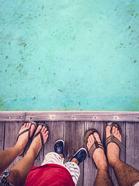 glückliche füße familie auf den malediven - salzwasser sandalen stock-fotos und bilder