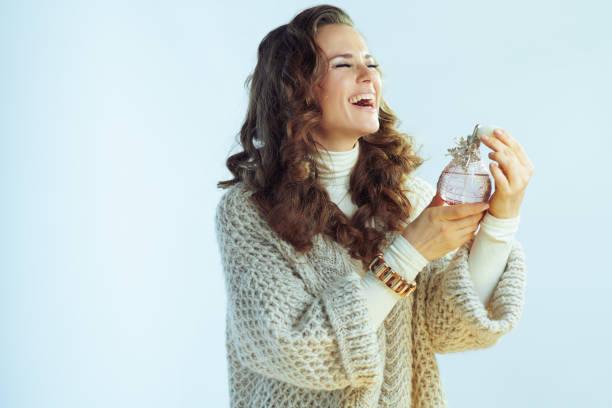happy female applying perfume on winter light blue background