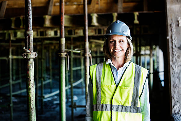 Happy female architect at construction site Portrait of happy female architect standing at construction site reflective clothing stock pictures, royalty-free photos & images