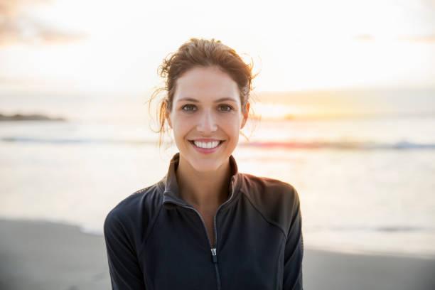 glücklich sportlerin am strand bei sonnenuntergang - damenjacken stock-fotos und bilder