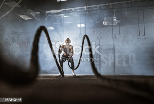 Young happy athletic woman having cross training with battle ropes in a health club. Copy space.