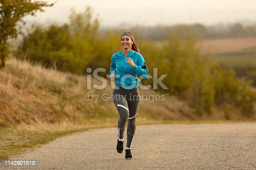 1142900322 istock photo Happy female athlete road running in the morning. 1142901510