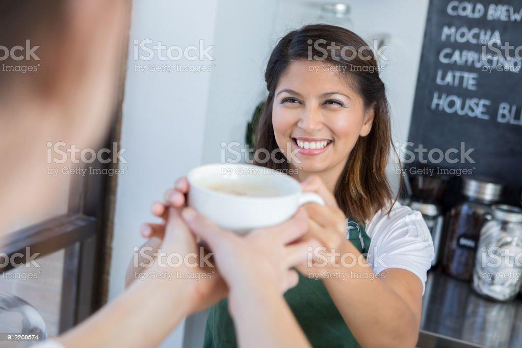 Happy female barista hands coffee to customer stock photo