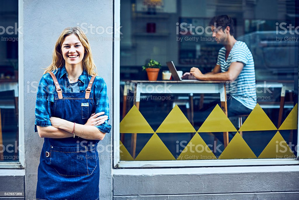 Happy female barista with arms crossed outside cafe stock photo