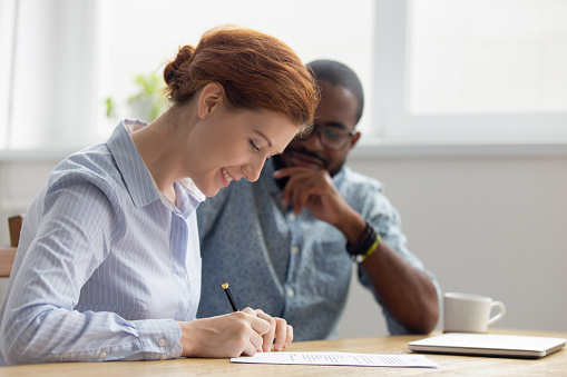 843533912 istock photo Happy female caucasian client signing contract meeting african american lawyer 1150384584