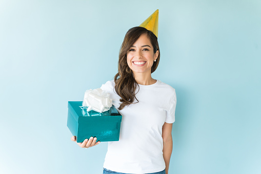 Excited beautiful woman with party hat holding birthday present over blue background