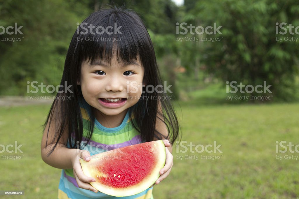 Happy female child holding a watermelon royalty-free stock photo